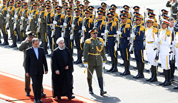 Iran's President Hassan Rouhani, second left, and Vice President Eshagh Jahangiri, left, review the honor guard