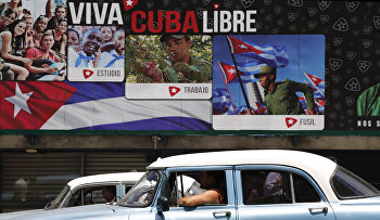 "A classic American car passes in front of some signs that reads in Spanish ""Long Live Free Cuba"" in Havana, Cuba"