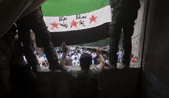 Free Syrian Army rebels hold a revolutionary flag during a demonstration in the Bustan al-Qasr neighborhood of Aleppo, Syria