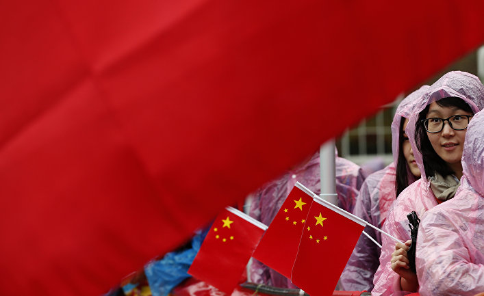 Supporters of Chinese President Xi Jinping hold up a large national flag of China