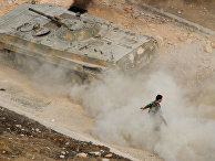 A Syrian APC moves raising dust in Harasta, northeast of Damascus, Syria