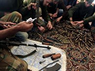 Free Syrian Army fighters clean their weapons and check ammunition