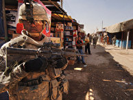 U.S. Army Staff Sgt. Jerrime Bishop provides security during a joint dismounted presence patrol with Iraqi National Police
