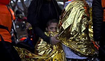 A boy is wrapped in an emergency thermal blanket after arriving on a rubber boat at a beach on the northern coast of Lesbos, Greece