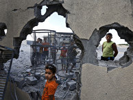 Palestinian Suma Abu Mahsen, 7, stands by a damaged wall of a house following an overnight Israeli missile strike