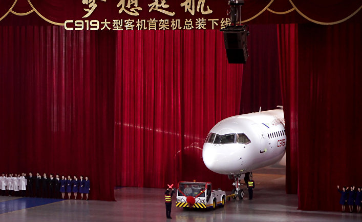 Chinese workers wave as a truck pulls out the first twin-engine 158-seater C919 passenger plane made by The Commercial Aircraft Corp. of China (COMAC)