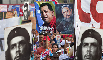 People hold up images showing Fidel Castro, second from right, Venezuela's late President Hugo Chavez