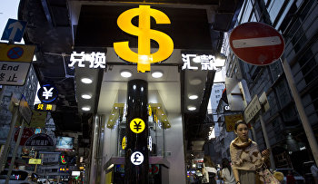 A woman walks near a dollar sign outside a money exchange shop in Hong Kong
