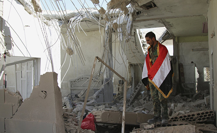 Syrian soldier wrapped in a Syrian flag stands in a damaged house in Achan, Hama province, Syria.