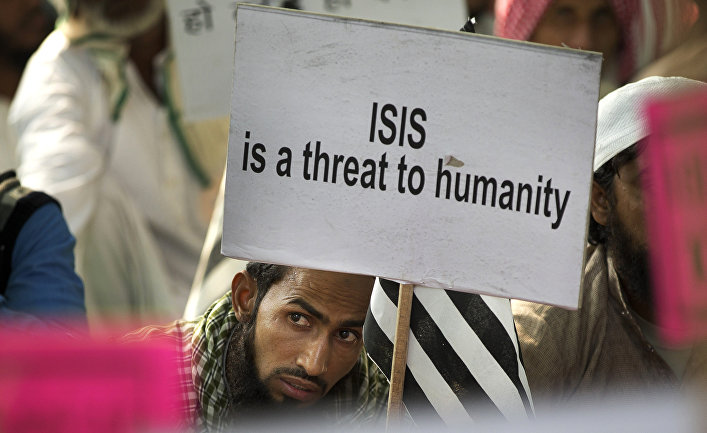 An Indian Muslim man holds a banner during a protest against ISIS