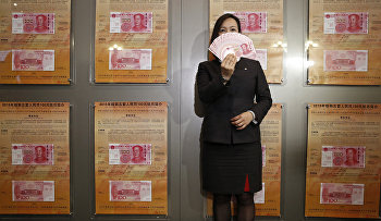 A staff member displays the new version of the 100-yuan RMB (US 15.7 dollars) banknotes for photographers at the Bank of China Tower in Hong Kong