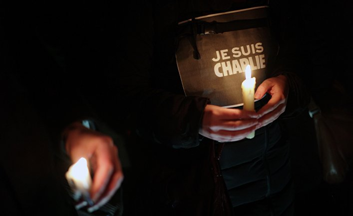 "People hold candles and a placard reading ""I am Charlie"" as they gather to commemorate the victims of a terror attack against French satirical newspaper Charlie Hebdo in Paris"