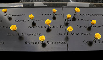 Yellow roses stand wedged into names carved in the granite at the South Pool of the National September 11 Memorial