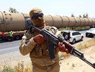 A Kurdish Peshmerga fighter stands guard as new equipment arrives at Kalak refinery on the outskirts of Irbil, Iraq