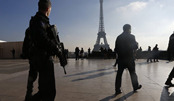 French police officers patrol near the Eiffel Tower, in Paris