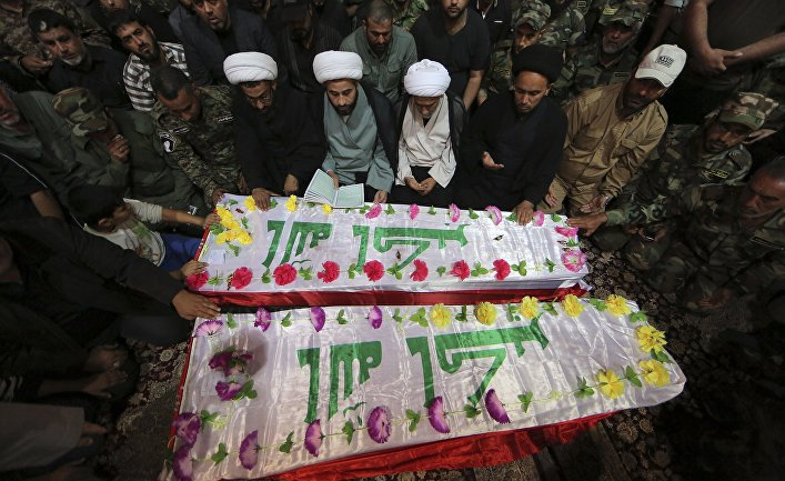 Mourners and militiamen pray around the flag-draped coffins of two members of the Peace Brigades