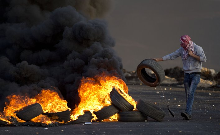 A Palestinian youth burns tires during clashes following a demonstration to demand the release of bodies of Palestinian attackers being held by Israeli authorities, in the West Bank city of Ramallah