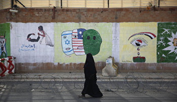 A woman walks past anti-Saudi and US graffiti sprayed on a wall of the closed Saudi embassy in Sanaa, Yemen