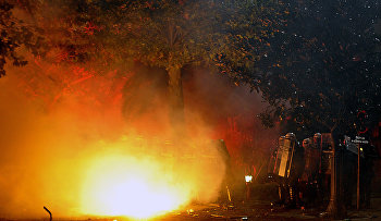 A torch hurled by opposition supporters bursts into flames while Montenegrin police officers stand during a protest in front of the Parliament building in Podgorica, Montenegro