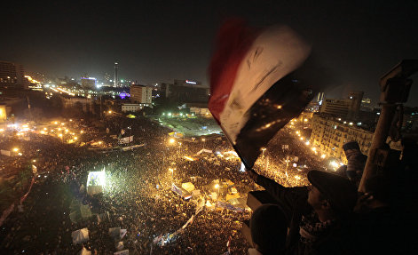 An Egyptian waves the national flag as he and others watch thousands of people gather in Tahrir Square to mark the first anniversary of the popular uprising that unseated President Hosni Mubarak, Cairo, Egypt, Wednesday, Jan. 25, 2012