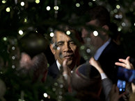 President Barack Obama is seen through holiday tree lights as he greets people in the audience during the second of two Hanukkah receptions the East Room of the White House in Washington