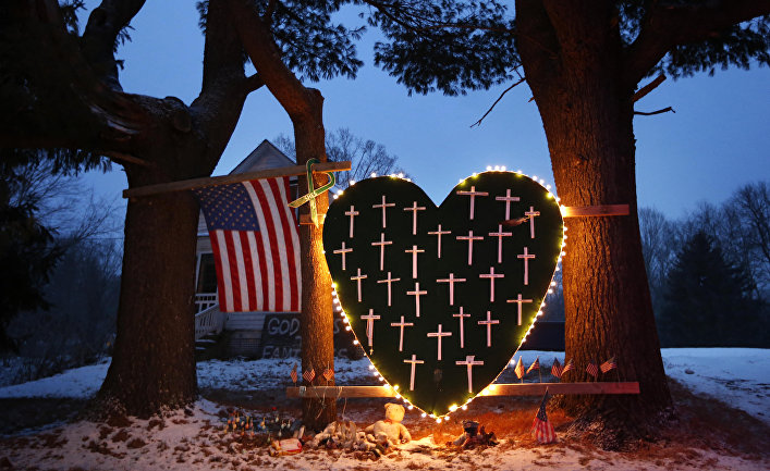 A makeshift memorial with crosses for the victims of the Sandy Hook Elementary School shooting massacre stands outside a home in Newtown, Conn