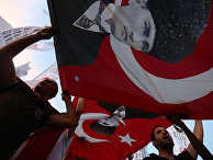 Men wave national flags with depictions of Turkey's founder Kemal Ataturk as they march to protest against the deadly attacks on Turkish troops, in Izmir, Turkey
