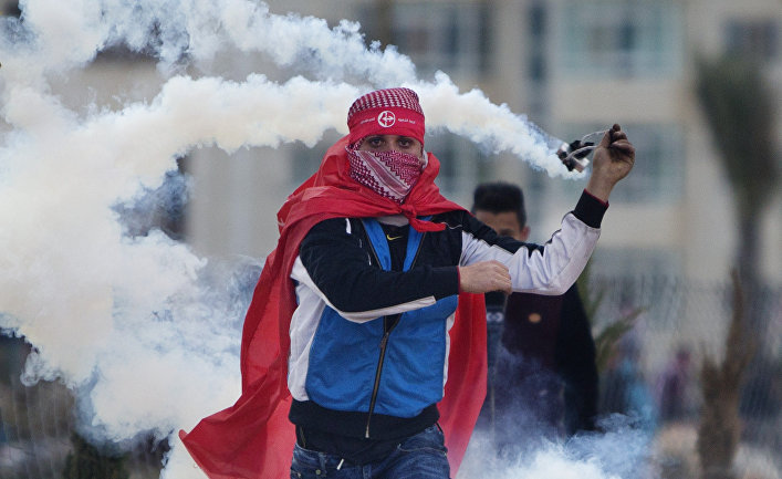 A Palestinian demonstrator uses a slingshot to throw back a tear gas canister at Israeli troops following a rally marking the 48th anniversary of the Popular Front for the Liberation of Palestine (PFLP), in the West Bank