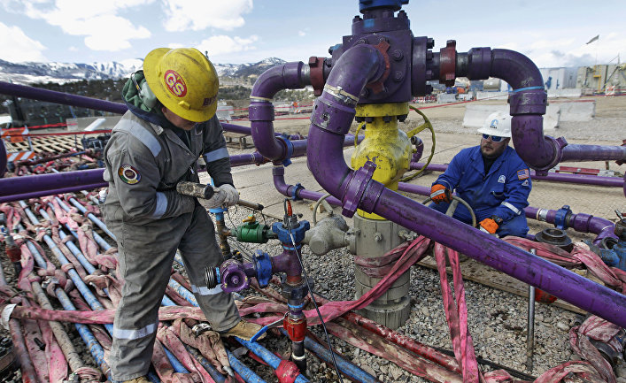 Workers tend to a well head during a hydraulic fracturing operation outside Rifle, in western Colorado.