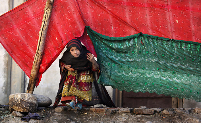 An internally displaced girl peeks from a tent after her family left their village in Rodat, Afghanistan. At least 25,200 families have been displaced across the province by Islamic State militants