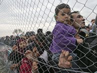 Stranded migrants, await entry into Macedonia on the Greek side of the border photographed through a fence from Macedonian side of the border, near the southern Macedonian town of Gevgelija