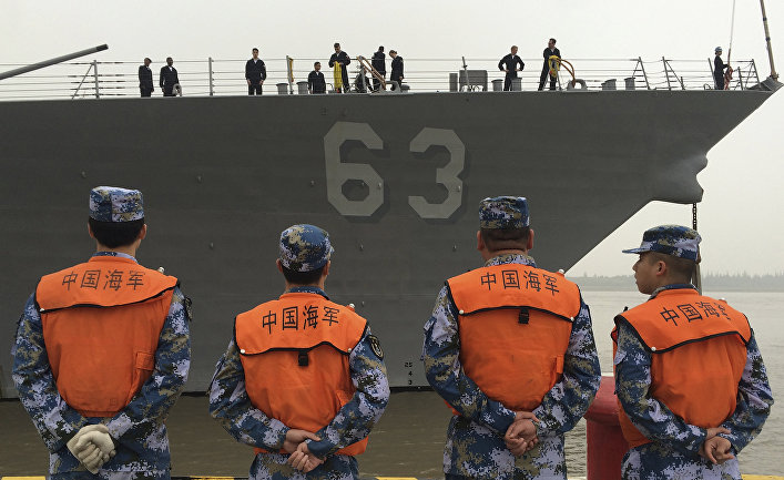 Chinese Navy personnel stand watch the guided missile destroyer USS Stethem arrives at the Shanghai International Passenger Quay for a scheduled port visit in Shanghai, China