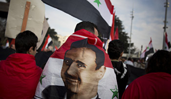 A Syrian demonstrator is wrapped in a Syrian flag outside the United Nations headquarters in Geneva, Switzerland