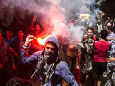 An Egyptian youth carries a lit flare as supporters of the Muslim Brotherhood gather in the El-Mataria neighborhood of Cairo, Egypt