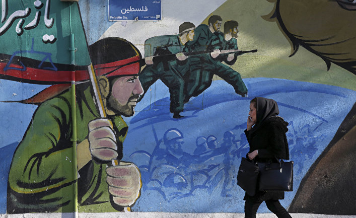 An Iranian woman walks past a mural depicting Iranian armed forces in the battlefield, at Palestine Sq. in Tehran, Iran, Saturday, Jan. 16, 2016.