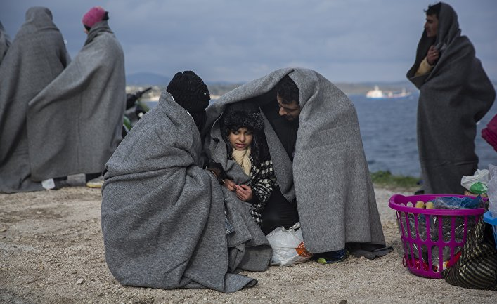 A family tries to keep warm with blankets, after the boat on which they crossed a part of the Aegean sea from Turkey hit on rocks, on the Greek island of Lesbos, on Saturday, Dec. 12, 2015