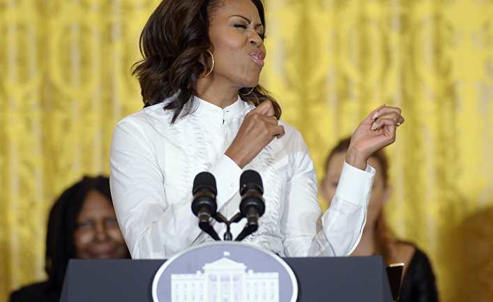 First lady Michelle Obama pretends to dance to music as she arrives to speak in the East Room of the White House in Washington, Friday, Nov. 8, 2013